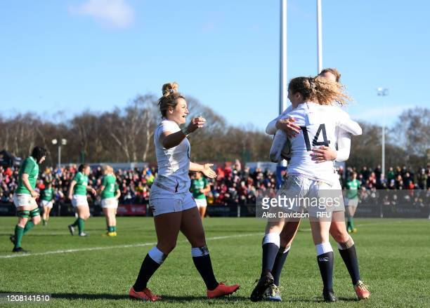 Abby Dow of England celebrates with teammates Amber Reed and Emily Scarratt after scoring her team's second try during the Women's Six Nations match...