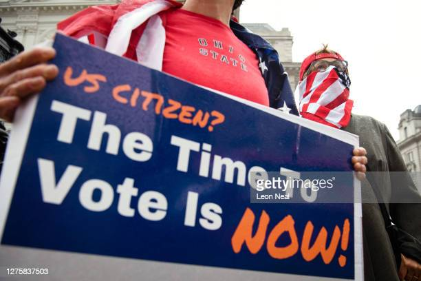 """Abby Taubin of """"Vote From Abroad"""" wears a US flag face mask as she attempts to sign up US citizens to vote in the upcoming US election, on September..."""