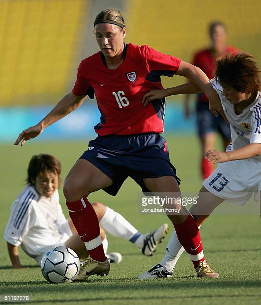 Abby Wambach of the United Sates dribbles the ball past Aya Shimokozuru of Japan competes in the women's football quarterfinal match on August 20...