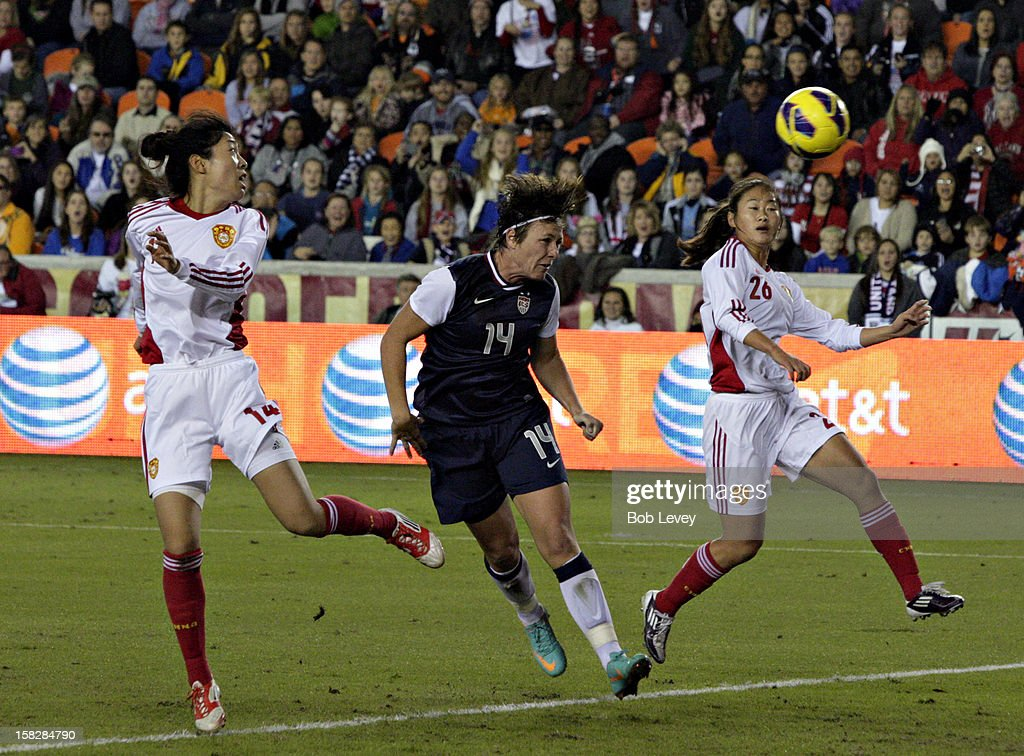 Abby Wambach #14 of the United States scores on a header as she gets between Wang Dongni #14 of China and Wu Haiyan #26 of China in the first half at BBVA Compass Stadium on December 12, 2012 in Houston, Texas.