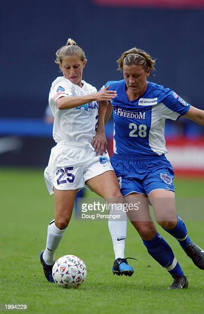 Abby Wambach of the Washington Freedom and Nancy Augustyniak of the Atlanta Beat battle for the ball during the WUSA match at RFK Stadium on April 26...