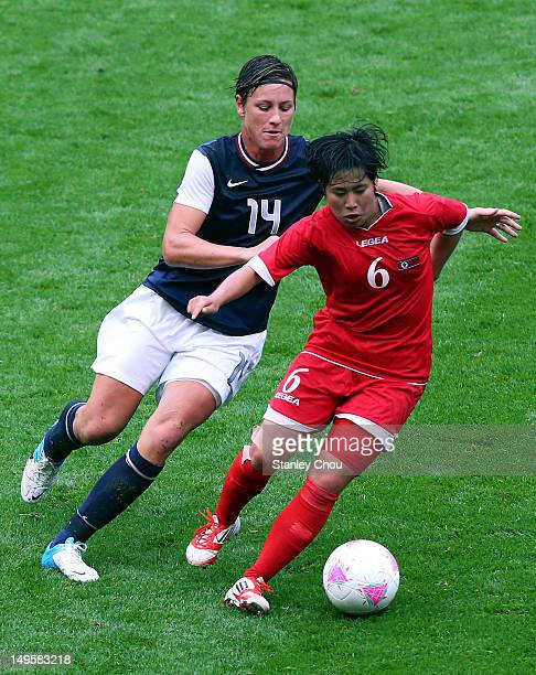 Abby Wambach of USA battles with Choe Un Ju of DPR Korea during the Women's Football first round Group G match between the United States and DPR...