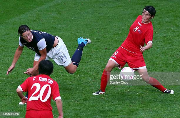 Abby Wambach of USA is tackled by Jon Myong Hwa of DPR Korea while Chou Yong Sim looks on during the Women's Football first round Group G match...