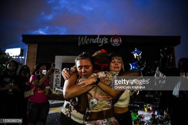TOPSHOT Abby Williams 28 and Alina Ferdinand 20 hus a woman as they protest outside a burned Wendy's restaurant on the third day following Rayshard...