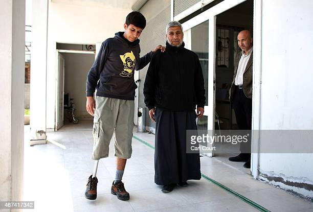 Abdalruhman AlHaji Deirzoor who lost his leg in a barrel bomb attack in Syria is helped by a volunteer as he learns to walk on a prosthetic leg...