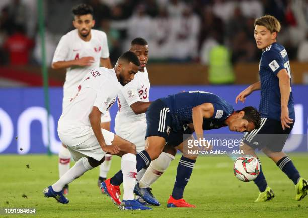 Abdel Aziz Hatim of Qatar battles with Yoshinori Muto of Japan during the AFC Asian Cup final match between Japan and Qatar at Zayed Sports City...