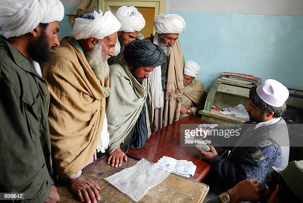 Abdel Fatah a cashier for the Kandahar bank counts the refund of $1500 US each for the Afghan men around his desk February 19 2002 who were supposed...