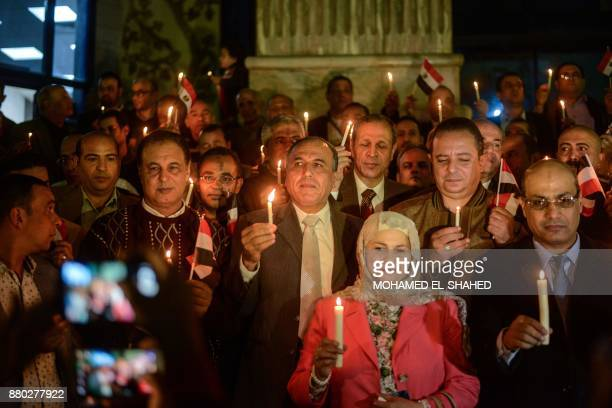 Abdel Mohsen Salama chief of the Egyptian Syndicate of Journalists speaks to the media as he holds a candle amongst others at a vigil outside...