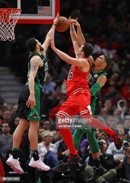 Abdel Nader of and Jayson Tatum of the Boston Celtics block a shot by Paul Zipser of the Chicago Bulls at the United Center on December 11 2017 in...