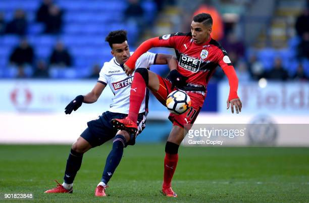 Abdelhamid Sabiri of Huddersfield Town is challenged by Derik Osede of Bolton Wanderers during the The Emirates FA Cup Third Round match between...