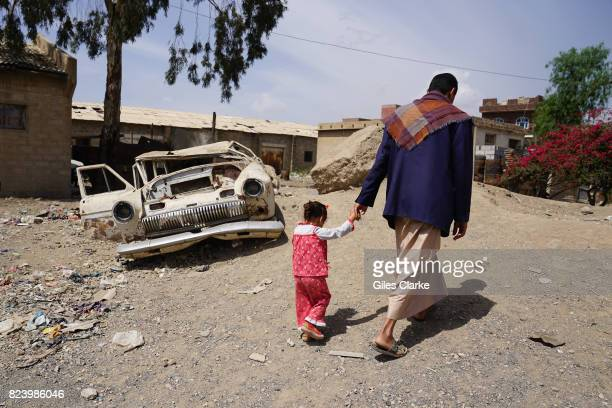A YEMEN 28 APRIL Abdellatif Allami walks with his 3yearold daughter Sara in the Harat AlMasna'a slum in Sana'a The slum sits next to a former textile...