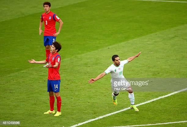 Abdelmoumene Djabou of Algeria celebrates after scoring his team's third goal as Yun SukYoung and Han KookYoung of South Korea react during the 2014...