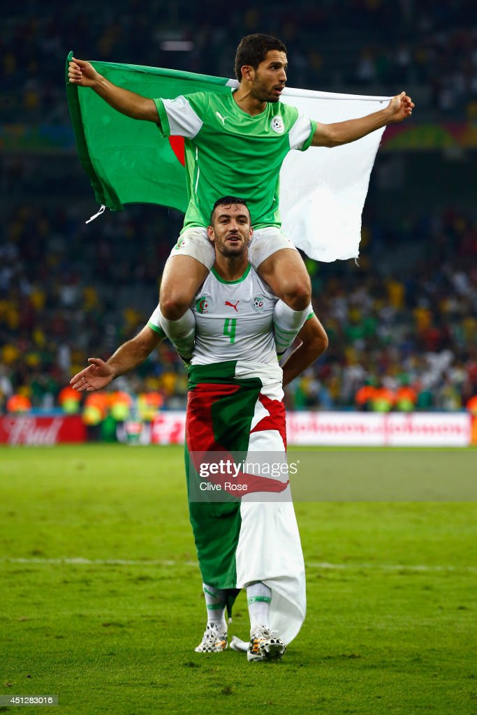 Abdelmoumene Djabou of Algeria celebrates on the shoulders of teammate Essaid Belkalem after a 1-1 draw during the 2014 FIFA World Cup Brazil Group H match between Algeria and Russia at Arena da Baixada on June 26, 2014 in Curitiba, Brazil.