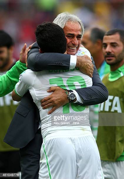 Abdelmoumene Djabou of Algeria celebrates scoring his team's third goal with head coach Vahid Halilhodzic during the 2014 FIFA World Cup Brazil Group...