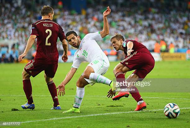 Abdelmoumene Djabou of Algeria is challenged by Aleksei Kozlov and Alexander Kokorin of Russia during the 2014 FIFA World Cup Brazil Group H match...