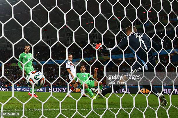 Abdelmoumene Djabou of Algeria scores his team's first goal past Manuel Neuer of Germany in extra time during the 2014 FIFA World Cup Brazil Round of...
