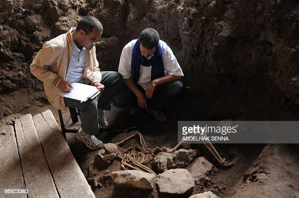 Abdelouahed BenNcer and Youssef Bokbot members of a Moroccan archaeology team take notes next to the 5000 year old human skeletons they discovered in...