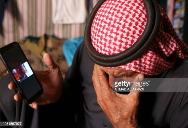 Abderrazaq Khatoun, reacts as he shows on a mobile telephone a video taken on the day when rescuers searched for survivors after an air raid that...