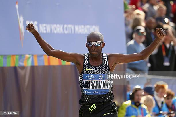 Abdi Abdirahman of the United States celebrates as he crosses the finish line to finish third in the Professional Men's Division during the 2016 TCS...