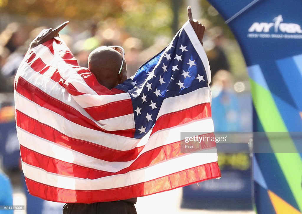 Abdi Abdirahman of the United States celebrates with the American flag after finishing third in the Professional Men's Division during the 2016 TCS New York City Marathon in Central Park on November 6, 2016 in New York City.