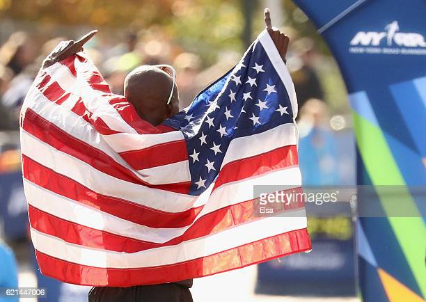 Abdi Abdirahman of the United States celebrates with the American flag after finishing third in the Professional Men's Division during the 2016 TCS...