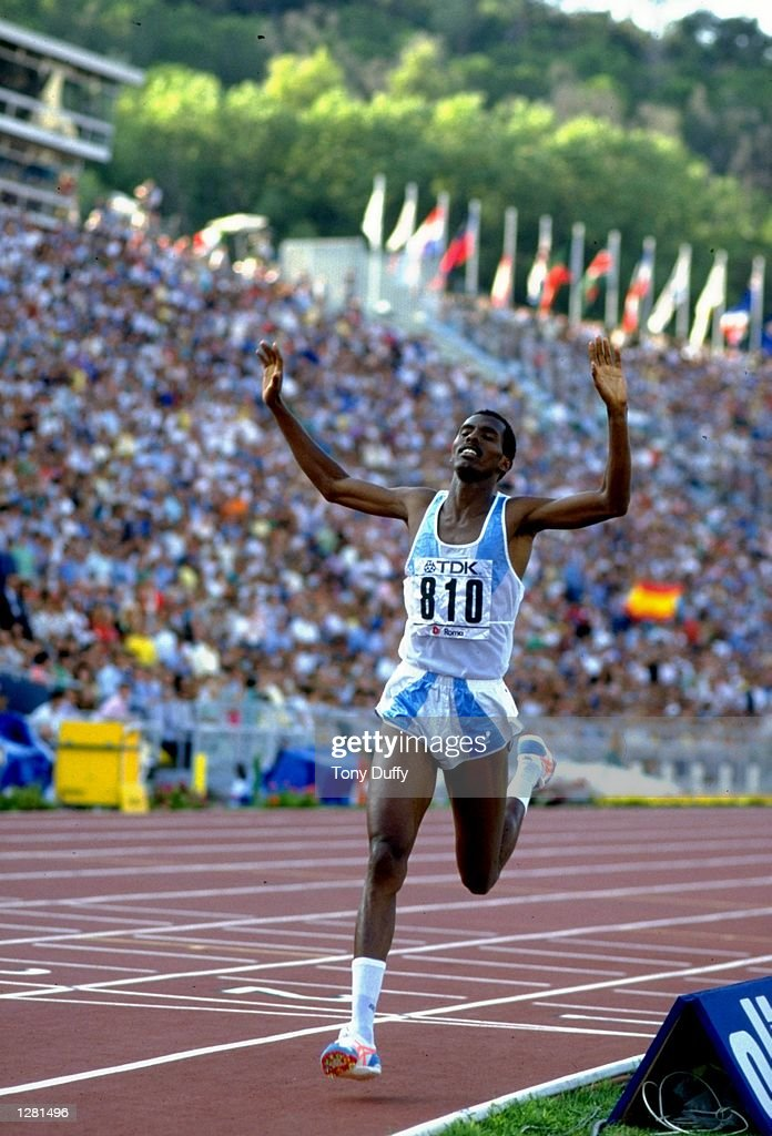 Abdi Bile of Somalia holds his arms aloft in celebration as he crosses the line to win the Mens 1500 metres event during the World Championships at the Olympic Stadium in Rome. \ Mandatory Credit: Tony Duffy/Allsport