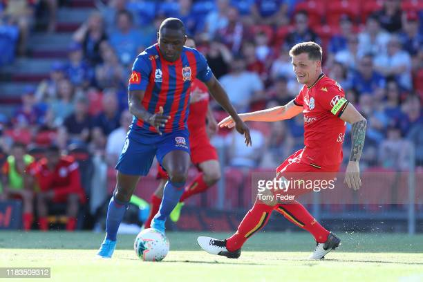 Abdiel Arroyo of the Newcastle Jets contests the ball with Michael Jakobsen of Adelaide United during the round three A-League match between the...