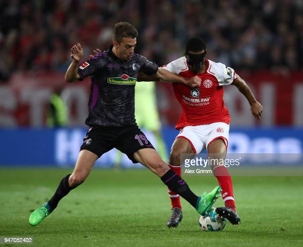 Abdou Diallo of Mainz is challenged by Janik Haberer of Freiburg during the Bundesliga match between 1 FSV Mainz 05 and SportClub Freiburg at Opel...