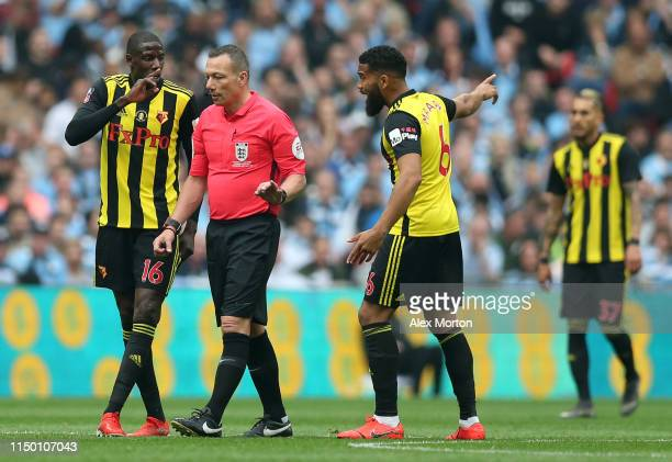 Abdoulaye Doucoure and Adrian Mariappa of Watford speak to Match Referee Kevin Friend during the FA Cup Final match between Manchester City and...
