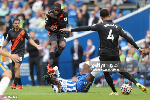 Abdoulaye Doucoure of Everton flinches and covers his body as he jumps over Yves Bissouma of Brighton & Hove Albion to avoid a clearance from Mason...