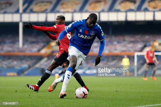 Abdoulaye Doucoure of Everton runs with the ball past Paul Pogba of Manchester United during the Premier League match between Everton and Manchester...