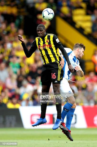 Abdoulaye Doucoure of Watford and Pascal Gross of Brighton and Hove Albion challenge for the ball during the Premier League match between Watford FC...