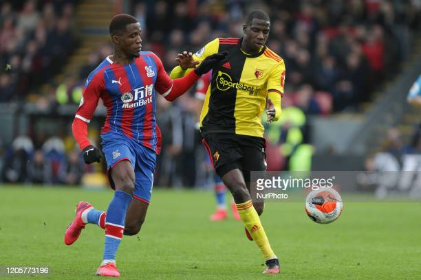 Abdoulaye Doucoure of Watford and Wilfried Zaha of Crystal Palace battling for possession during the Premier League match between Crystal Palace and...