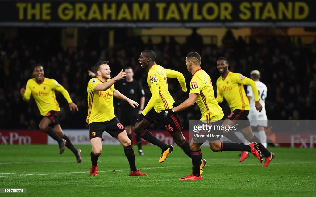 Abdoulaye Doucoure (C) of Watford celebrates the own goal scored by Kasper Schmeichel of Leicester City with team mates during the Premier League match between Watford and Leicester City at Vicarage Road on December 26, 2017 in Watford, England.