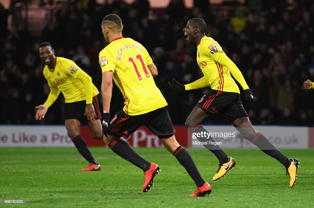 Abdoulaye Doucoure (R) of Watford celebrates the own goal scored by Kasper Schmeichel of Leicester City with team mates during the Premier League match between Watford and Leicester City at Vicarage Road on December 26, 2017 in Watford, England.