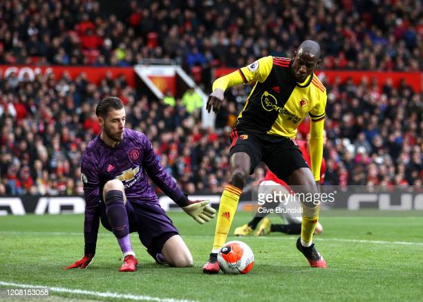 Abdoulaye Doucoure of Watford controls the ball in front of David De Gea of Manchester United during the Premier League match between Manchester...