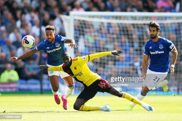 Abdoulaye Doucoure of Watford falls in a battle with Theo Walcott and Andre Gomes of Everton during the Premier League match between Everton FC and...
