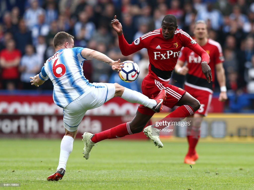 Abdoulaye Doucoure of Watford is challenged by Jonathan Hogg of Huddersfield Town during the Premier League match between Huddersfield Town and Watford at John Smith's Stadium on April 14, 2018 in Huddersfield, England.