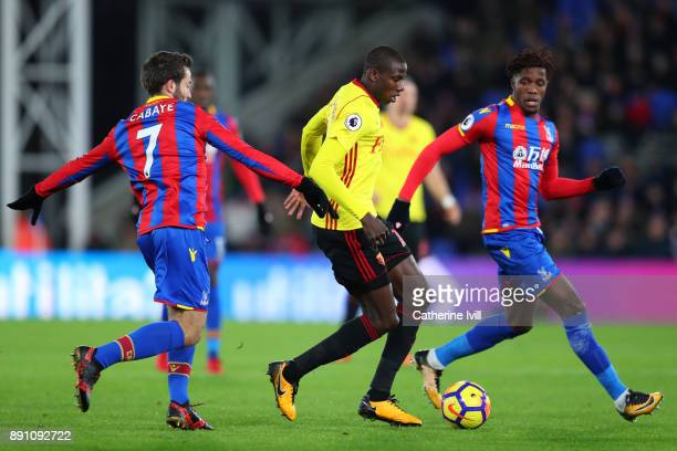 Abdoulaye Doucoure of Watford is tackled by Yohan Cabaye and Wilfried Zaha of Crystal Palace during the Premier League match between Crystal Palace...
