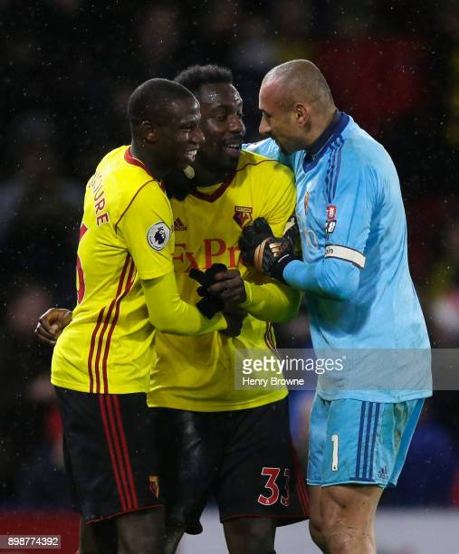 Abdoulaye Doucoure Stefano Okaka and Heurelho Gomes of Watford celebrate victory after the Premier League match between Watford and Leicester City at...