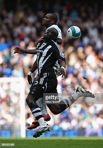 Abdoulaye Faye of Newcastle jumps for the ball ith Darren Bent of Tottenham during the Barclays Premier League match between Tottenham Hotspur and...