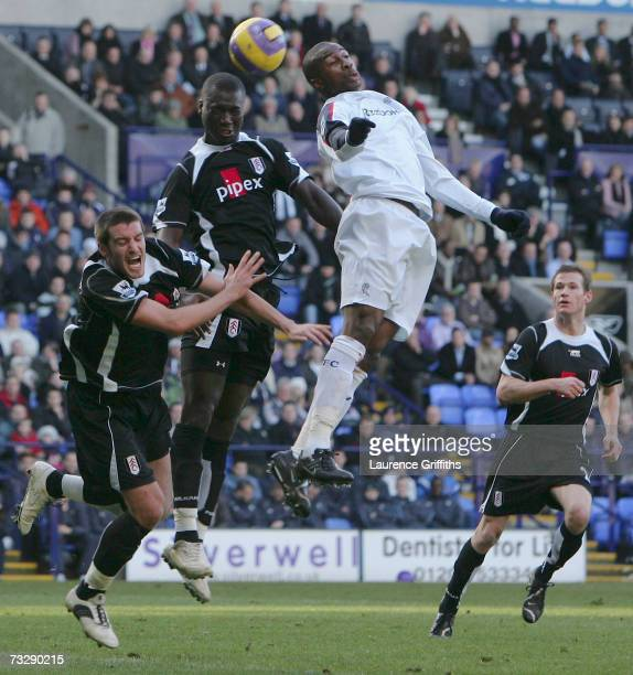 Abdoulaye Meite of Bolton Wanderers jumps for the ball with Franck Queudrue and Papa Bouba Diop of Fulham during the Barclays Premiership match...