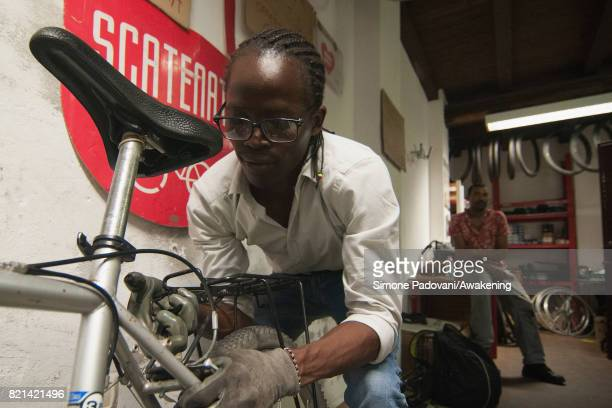 Abdoulaye repairs a bicycle at the bicycle workshop where he helps as volunteer on July 21 2017 in Bologna Italy Abdoulaye Diallo a Muslim was born...