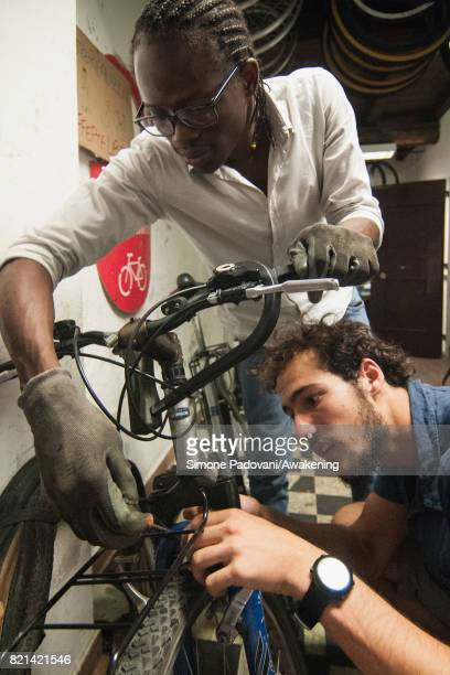 Abdoulaye repairsa bicycle with a citizen at the bicycle workshop where he helps as volunteer on July 21 2017 in Bologna Italy Abdoulaye Diallo a...