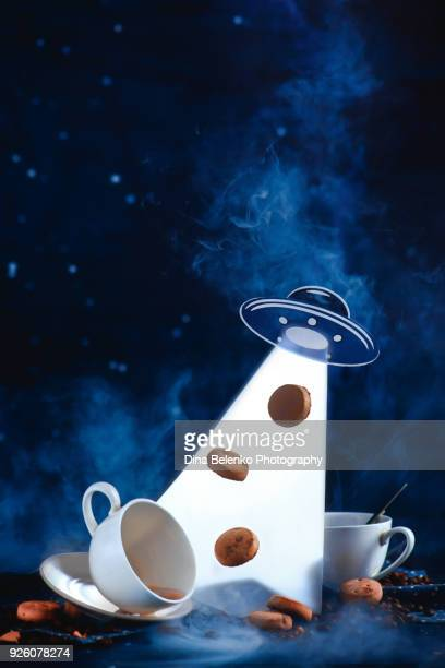 UFO abduction with cookies and teacups. Mystical science fiction still life with papercraft. Levitating food with copy space.
