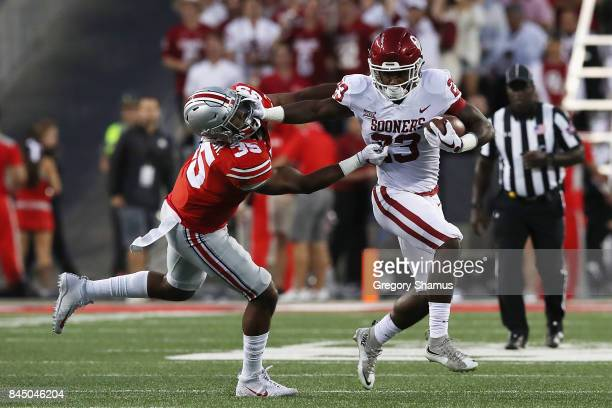 Abdul Adams of the Oklahoma Sooners stiff arms Chris Worley of the Ohio State Buckeyes during the first half of their game at Ohio Stadium on...