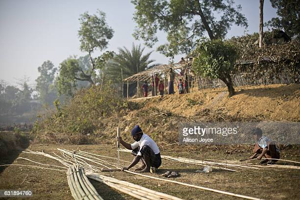 Abdul Amin and his son work to construct their house the Balu Kali refugee camp on January 17 2017 in Cox's Bazar Bangladesh Abdul Amin and his...
