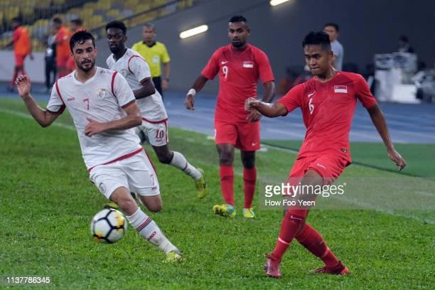 Abdul Aziz Humaid Mubarak of Oman nd Muhammad Amirul Adli of Singapore in action during the Airmarine Cup final between Singapore and Oman at Bukit...