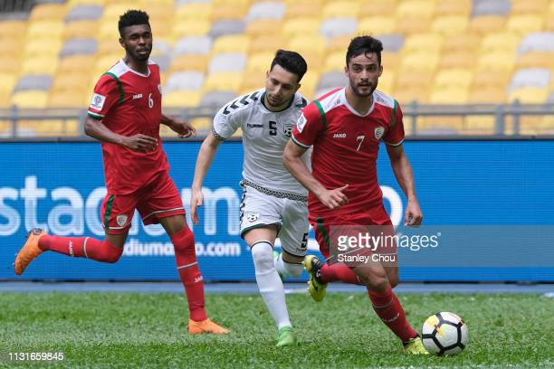Abdul Aziz of Oman holds off Adam A Najem of Afghanistan during the Airmarine Cup match between Oman and Afghanistan at Bukit Jalil National Stadium...
