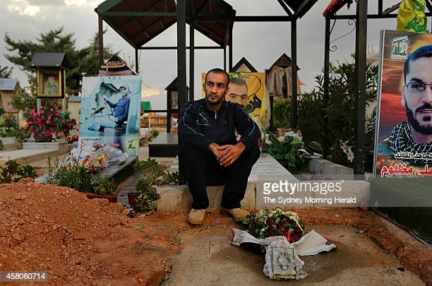 Abdul Ghani Saleh sits at the grave of his brother Ahmad Saleh in the Hezbollah martyr cemetery in Brital village in the Bekaa Valley Lebanon October...